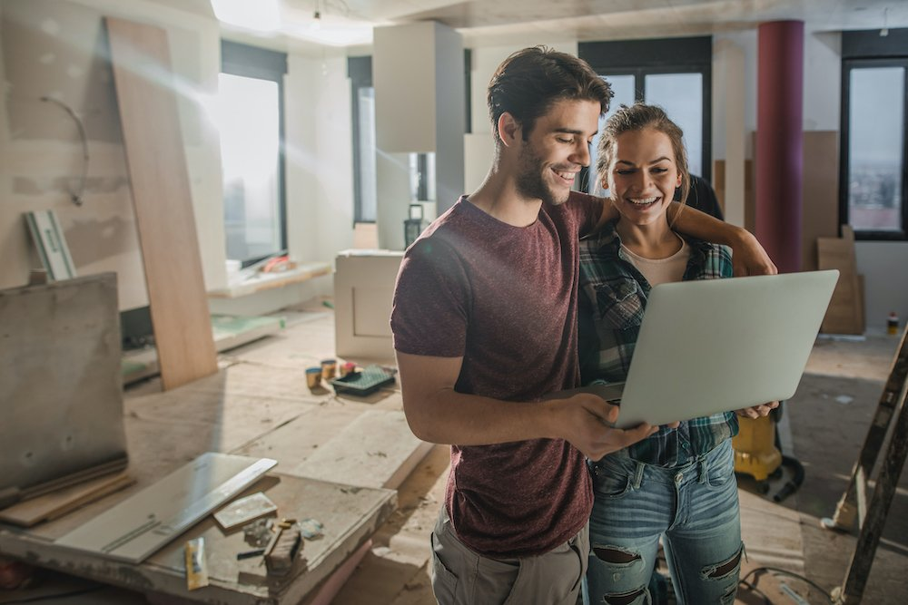 Young happy couple surfing the Internet on a computer during home renovation process.